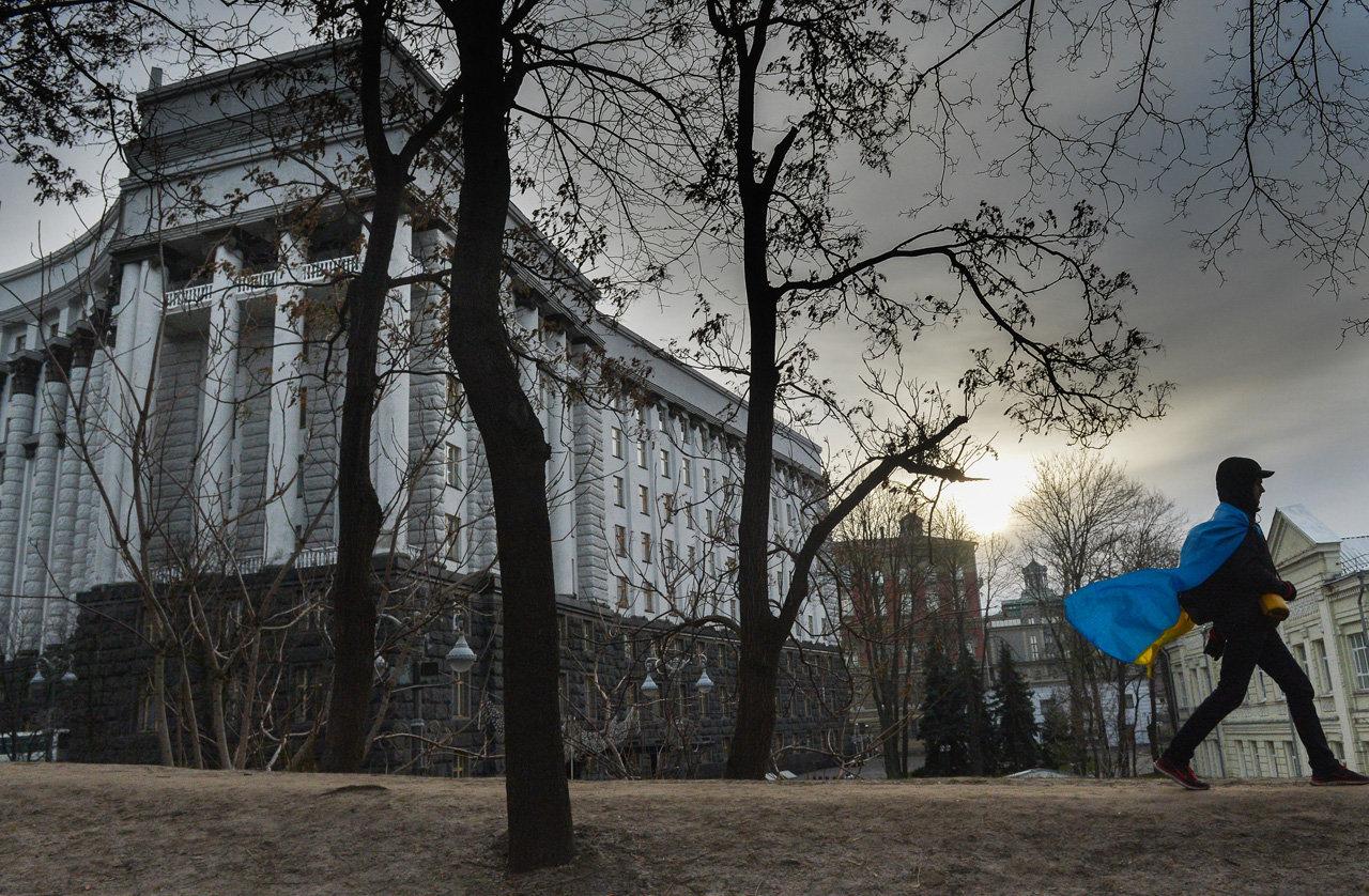 Сторонник евроинтеграции Украины проходит мимо здания правительства после рассмотрения вопроса об отставке правительства Николая Азарова