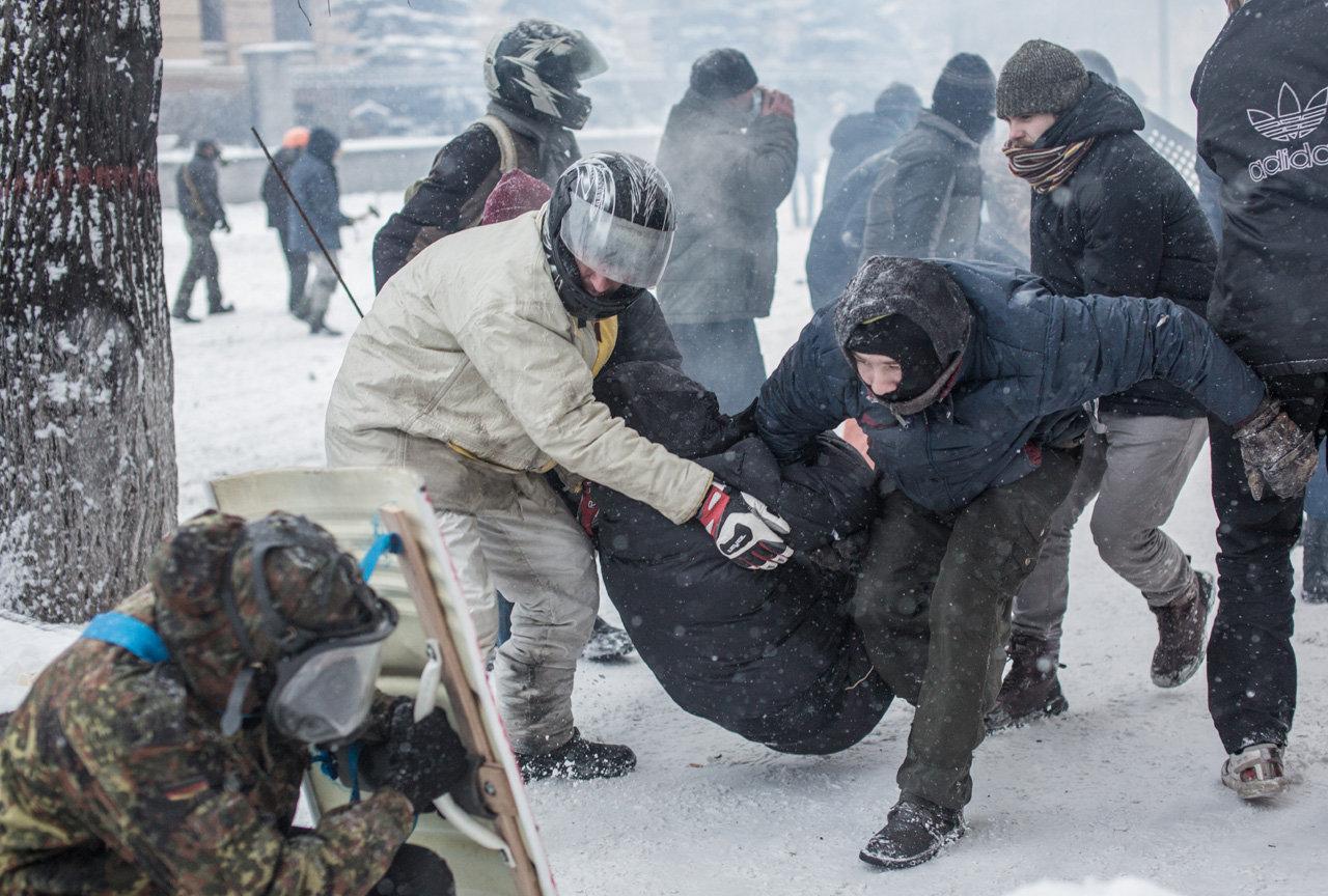 Протестующие выносят своего раненого товарища на улице Грушевского в Киеве