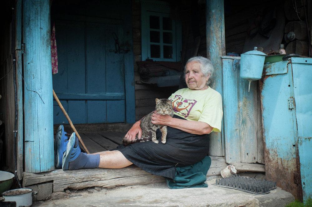 Бабулька гладзіць ката на ганку сваей хаты ў вёсцы Палясціна Астравецкага раёна