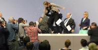 СПУТНИК_Девушка с криком запрыгнула на стол главы ЕЦБ во время пресс-конференции