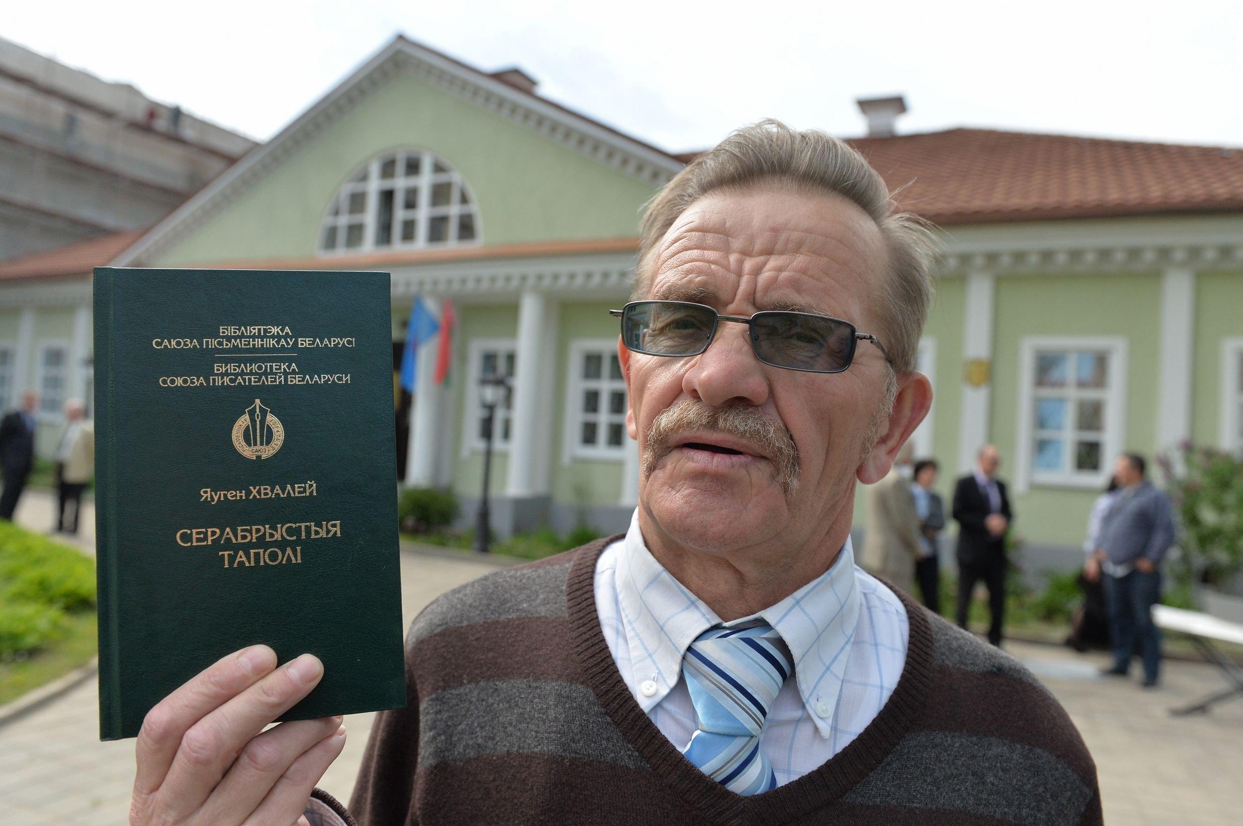 Беларускі пісьменнік Яўген Хвалей са сваёй кнігай Серабрыстыя таполі