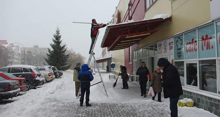 Очистка снега с козырька у входа в торговый центр
