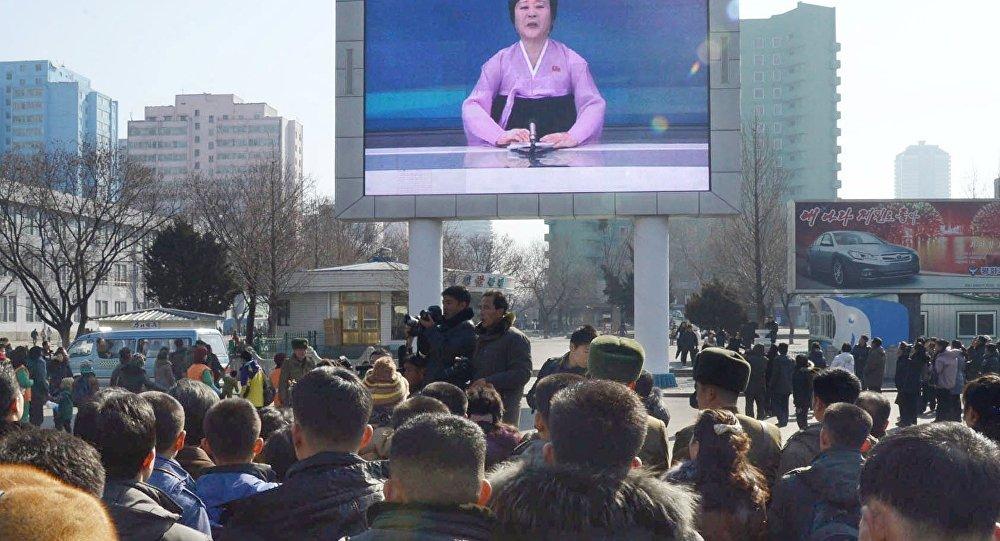 Жители Пхеньяна смотря на экране объявление о запуске ракеты