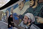 Иранская женщина идет мимо революционного мурала в Тегеране