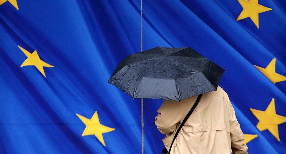 Женщина под зонтом возле Еврокомиссии в Брюсселе