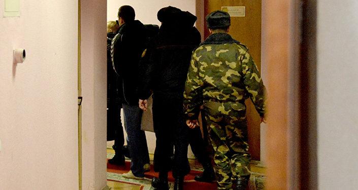 Заключенных ведут по коридору суда
