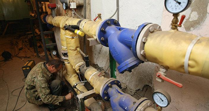 Сантехник красит трубу на тепловом узле в подвале одного из жилых домов. Архивное фото
