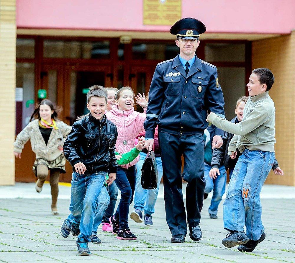 Инспектор ИДН и дети возле школы
