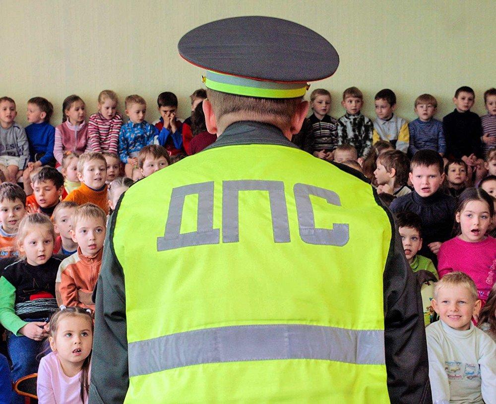 Сострудник ДПС объясняет правила дорожного движения детям