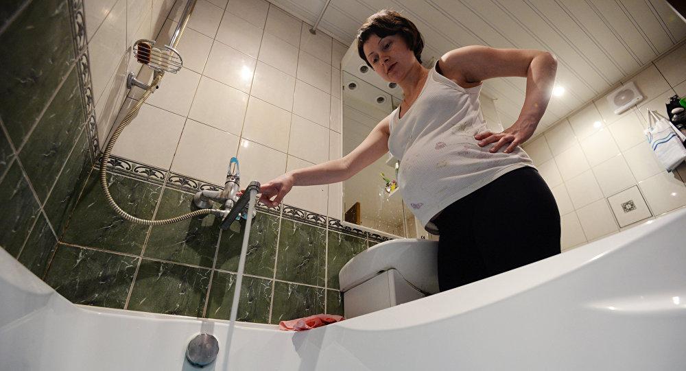 Беременная женщина набирает воду в ванной комнате