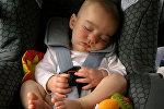 Ребенок спит в детском автомобильном кресле. Архивное фото