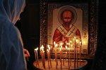 Жанчына каля іконы Мікалая Цудатворцы