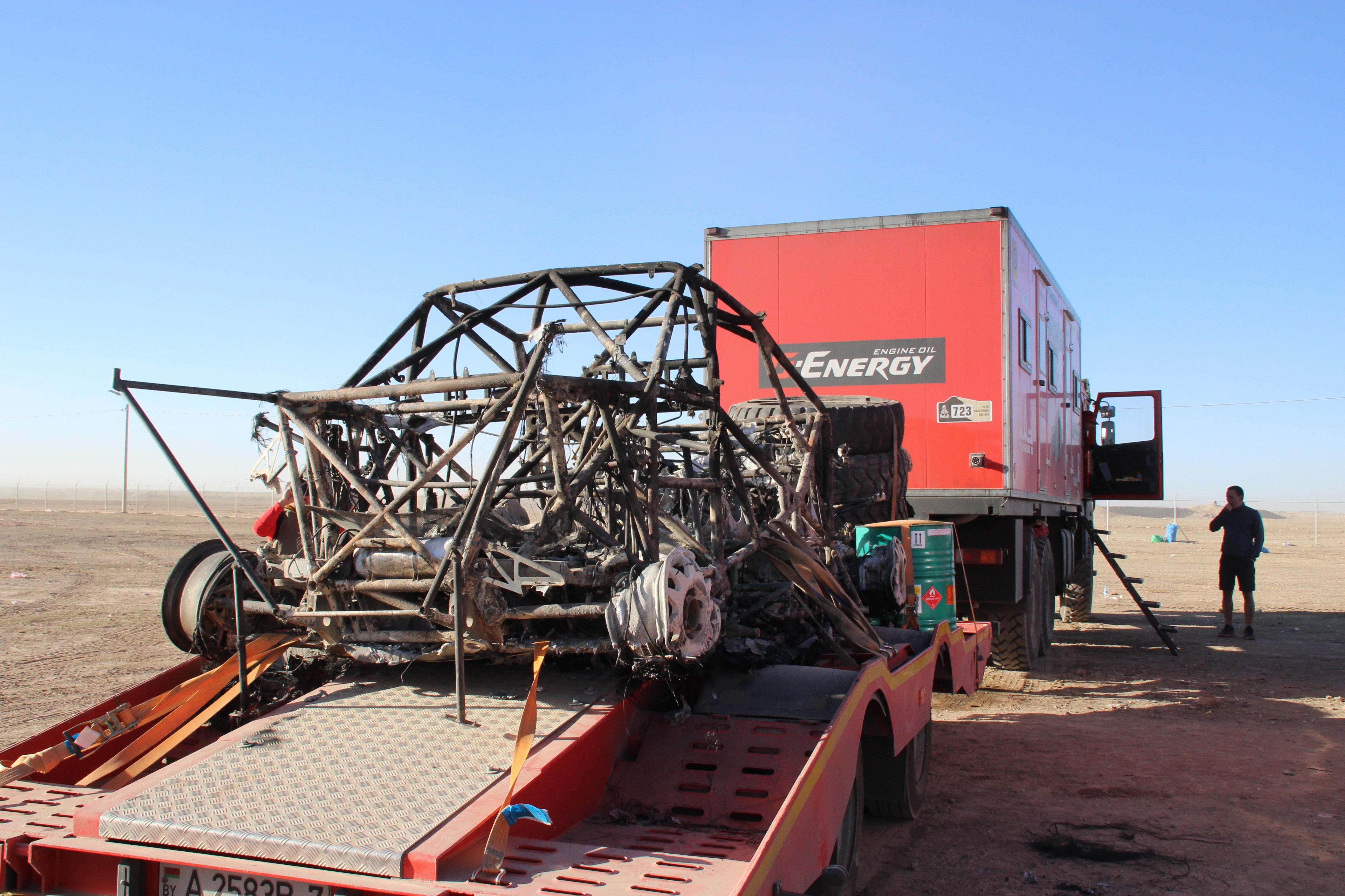 Остов сгоревшего внедорожника на лафете машины технического сопровождения МАЗ-СПОРТавто