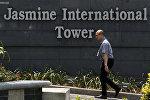 Человек проходит мимо логотипа Jasmine International Tower в Бангкоке