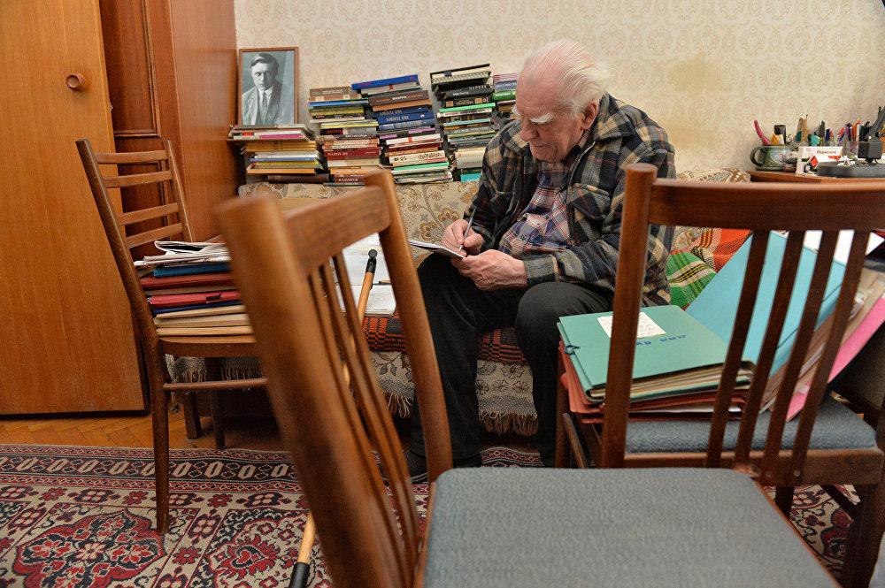 Народны паэт Беларусі падпісвае кнігу ў сваёй кватэры, 2015 год.