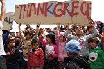СПУТНИК_Беженцы с детьми вышли с плакатами на митинг в Хиосе против их выдачи Турции