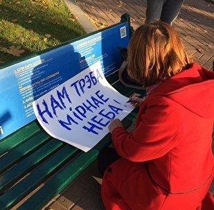 Женщина рисует плакат перед митингом За Беларусь без иностранных военных баз