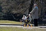 Дедушка гуляет в парке с внуками
