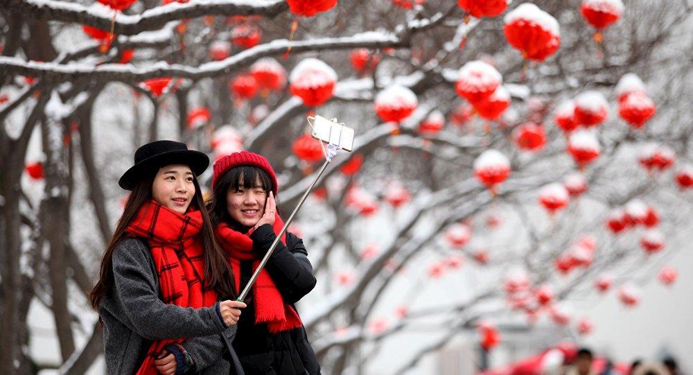 Туристки делают селфи после снегопада в Сиане