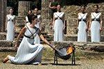 Верховная жрица зажигает олимпийский факел с помощью параболического зеркала, которое фокусирует лучи Солнца