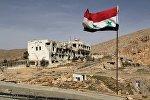 Флаг Сирии на фоне полуразрушенного здания