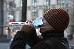 Мужчина в защитной маске пьет водку.