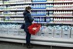 Покупатель у прилавка с молочной продукцией в магазине, архивное фото