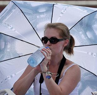 Женщина прячется от солнца под зонтом