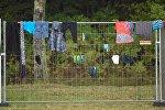 Одежда мигрантов весит на заборе в лагере для беженцев в городе Целле (Германия)