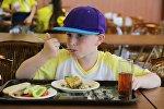 Мальчик обедает в столовой лагеря