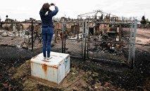 Женщина фотографирует сгоревший дом в городе Форт-Мак-Мюррей в провинции Альберта (Канада)