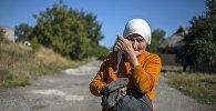 Мясцовая жыхарка назірае за праходам калоны машын 38-га гуманітарнага канвояў Данецкай вобласці