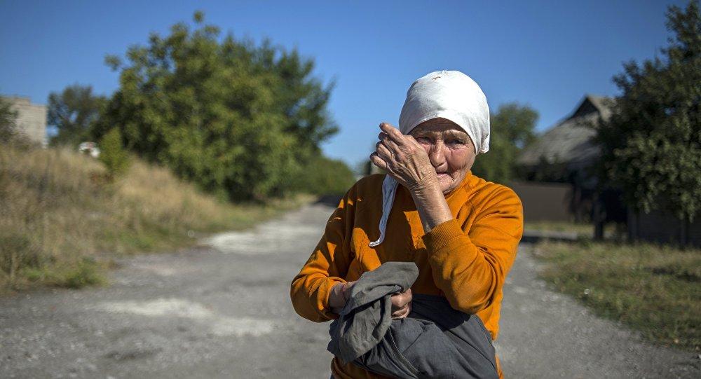 Местная жительница наблюдает за проходом колонны машин 38-го гуманитарного конвоя в Донецкой области