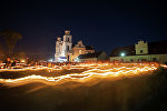 Ночное шествие с копией иконы Будславской Божьей матери и свечами перед костелом.