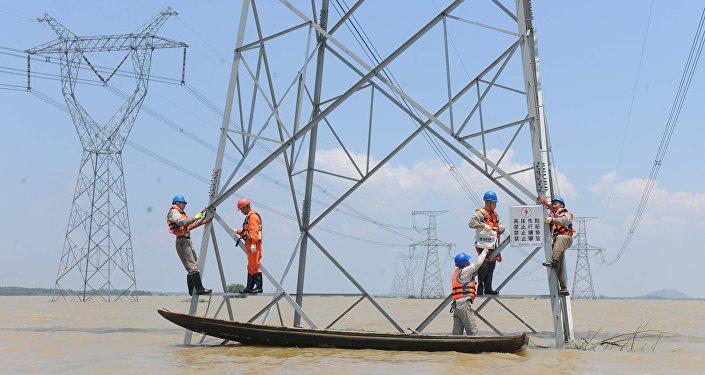 Рабочие укрепляют опоры линий электропередач в зоне подтопления тайфуна  Nepartak