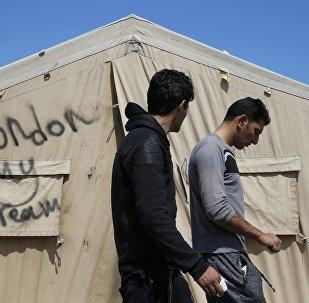 Мигранты идут мимо палатки в лагерье иммигрантов в Кале, Франция