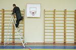 Учитель труда ремонтирует шведскую стенку, архивное фото