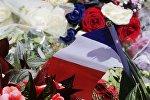 Цветы и французский флаг недалеко от места теракта в Ницце
