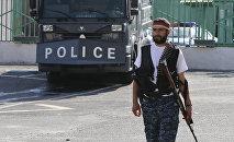 Вооруженный человек возле здания ППС, захваченного членами группировки Сасна црер