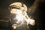 Электрик устанавливает энергосберегающие лампы