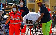 Спасатели транспортируют труп погибшего в результате землетрясения