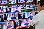 Мужчина смотрит выпуски новостей об испытании ядерного оружия в КНДР