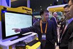 Техник объясняет посетителям работу сети 5G на стенде SK Telecom, на Всемирном конгрессе мобильной связи в Барселоне 22 февраля