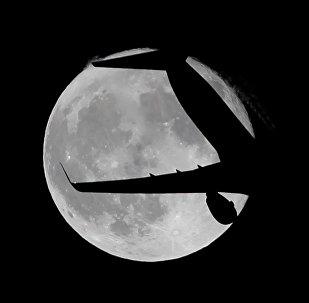 Пассажирский самолет Ryanair пролетает на фоне суперлуны