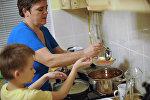 Мать разливает по тарелкам суп