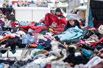 Покупатели выбирают вещи секонд-хэнд на рынке Ждановичи