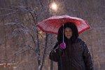 Женщина с зонтом идет по улице во время снегопада
