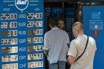 Люди стоят в очереди за пределами обмена валют в Алматы