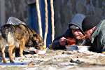 Бомжи едят горячий обед, который раздают волонтеры