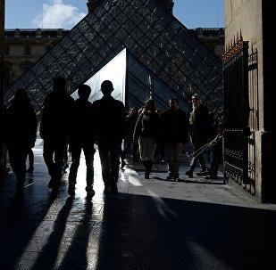 Прохожие у стеклянной пирамиды Лувра